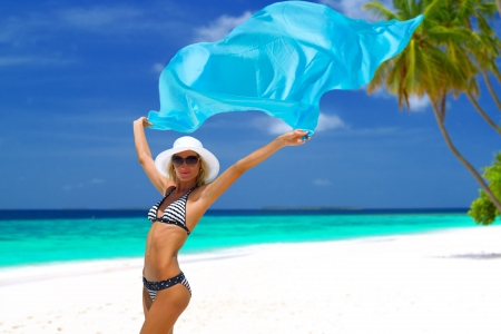 Mooie bikini model met blauwe sjaal poseren op wit zandstrand met palmbomen en turquoise water op de Maldiven Stockfoto