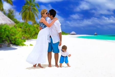 Happy family of three having tropical vacation on Maldives. Parents with baby kissing on the beach. photo