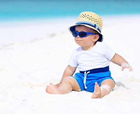 Baby with hat and sunglasses sitting on the tropical beach Stockfoto