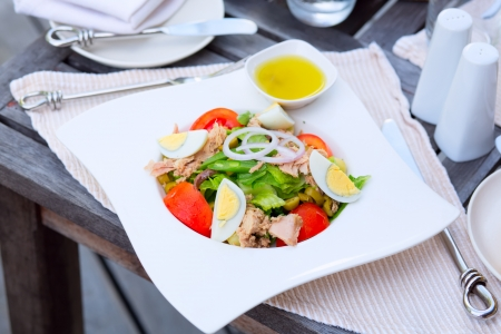 Nicoise Salad with canned tuna, anchovies, hard boiled eggs, tomatoes, olives, onions, lettuce, and green beans. French cuisine photo