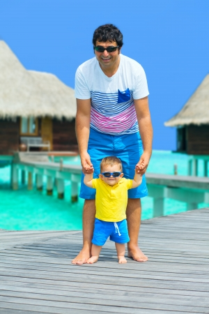 Happy Father and baby boy having fun on Maldives, walking on the bridge to water villas photo