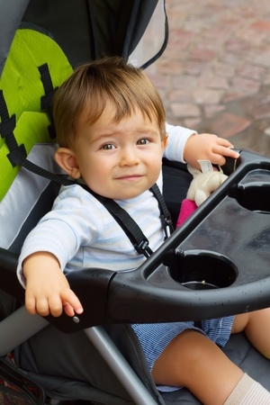 Cute Baby boy sitting in stroller outdoors photo