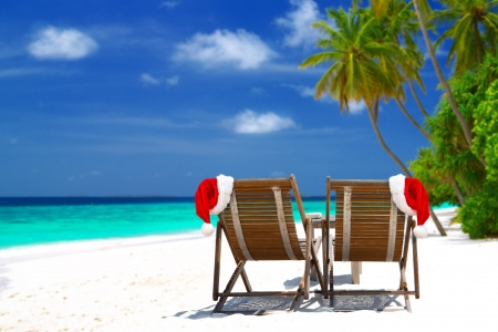 maldives beach: Christmas card or background - two sunloungers with Santa hats standing on beautiful tropical beach with palm trees, white sand and turquoise water on Maldives. Concept of perfect vacation.  Stock Photo