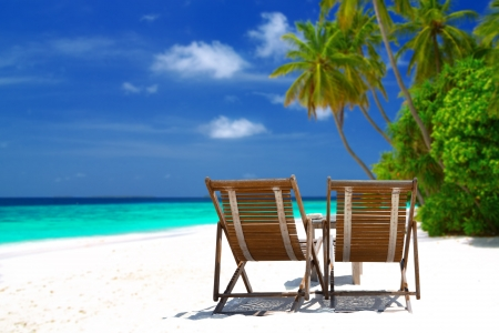 Tropical background - two sunloungers standing on beautiful tropical beach with palm trees, white sand and turquoise water on Maldives. Concept of perfect vacation.  Stock Photo