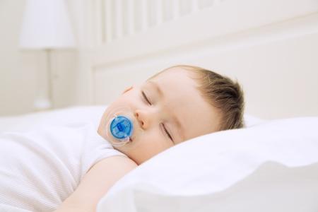 Adorable schlafenden Baby auf dem Kissen mit Schnuller, close up drinnen erschossen
