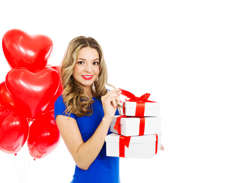 Beautiful blond woman smiling and holding gift boxes with red heart shaped balloons, valentines day. Half body portrait, isolated, over white background with copy space. photo
