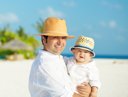 Father and son with panama hats stands on white sandy beach on Maldives photo