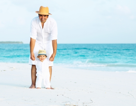 Happy father and son with panama hats on the tropical beach photo