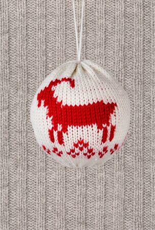 woll: Knitted Christmas Ball with on woll knitted background with copy space