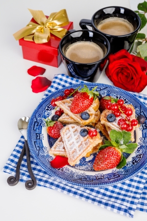 Heart shaped waffles and coffee for romantic breakfast with strawberries, red rose and gift box, valentines day photo