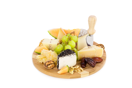 Cheese plate with grapes and dry fruits. Over white background, isolated, with copy space. photo