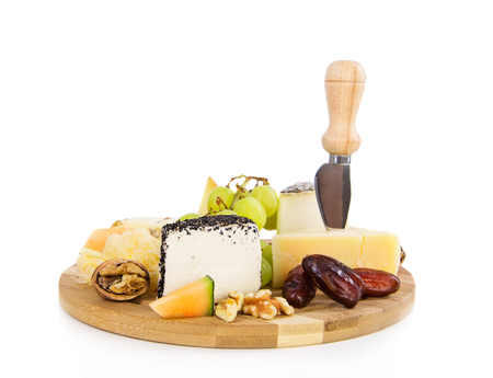 Variety of swiss chees on a plate with walnut, grapes and dates photo