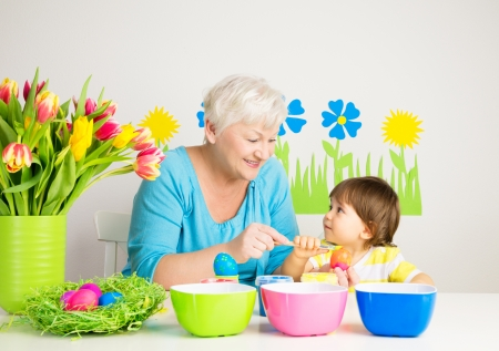 Happy grandmom and grandson color eggs for Easter at home Stock Photo - 25236389