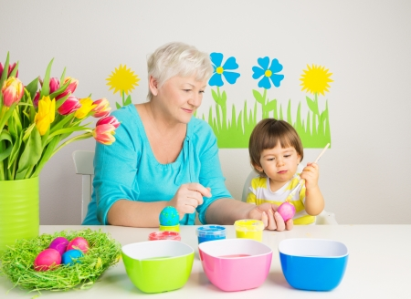 Loving grandma teaching her grandson to color eggs for Easter at home photo