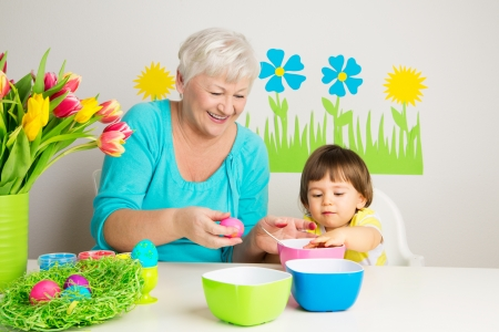grandmother grandchild: Happy grandmom and grandson color eggs for Easter at home