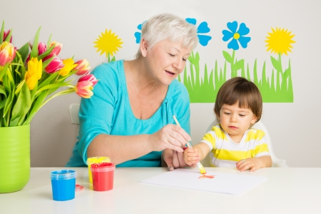 Loving grandma teaching her grandson to draw with paint at home photo
