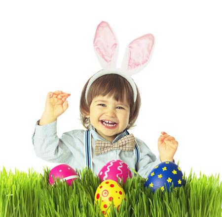 Lachende baby jongen met bunny oren, vlinderdas, bretels jacht voor Pasen eieren in een groen gras. Retro fashion stijl. Studio-opname, geïsoleerd, op een witte achtergrond met een kopie ruimte.