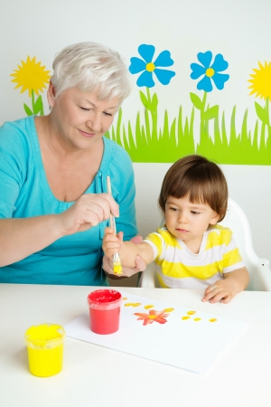 Loving grandmother teaching her grandson to draw with paint at home photo