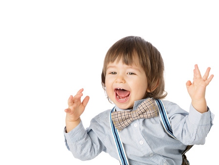 Playful happy baby boy, Child Model with romantic Fashion outfit suspenders and tie bow, delighted and smiling. Studio shot, isolated, over white background with copy space photo