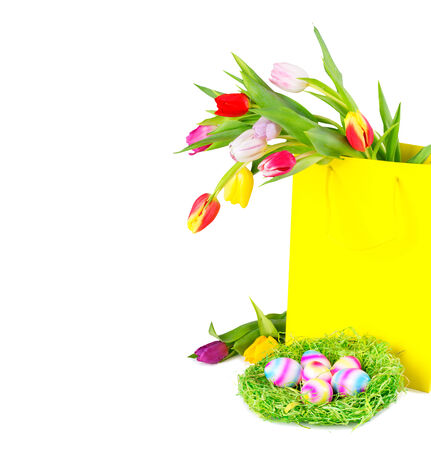 Colorful tulips in yellow shopping bag with easter eggs in the nest, over white background, with copy space, isolated. photo