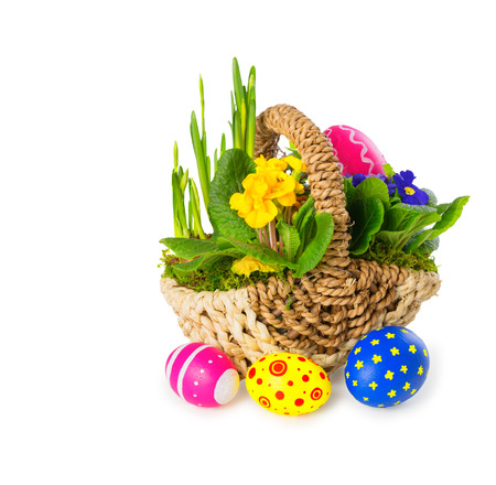 Basket of colorful spring flowers with handmade eastereggs, isolated, over white background, with copy space photo