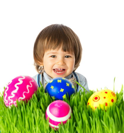 Cute Baby boy hunting for colorful Easter Eggs, hidden in the green grass, close up face portrait. Studio shot, over white background, isolated, with copy space. photo