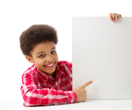 African American school boy, teenager smiling and ponting at empty white blank board, education and school concept. Isolated, over white, with copy space. photo