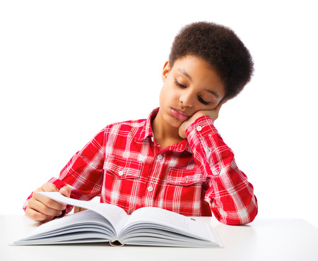 Bored African American school boy reading book without interest, education and school concept.