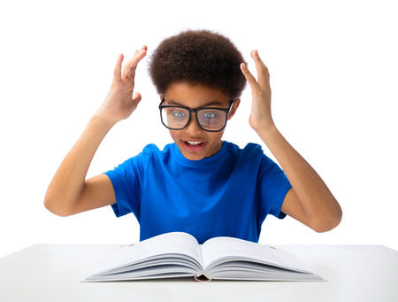 African American school boy, teenager studying hard, education and school concept - little student boy with book and glasses.  Фото со стока