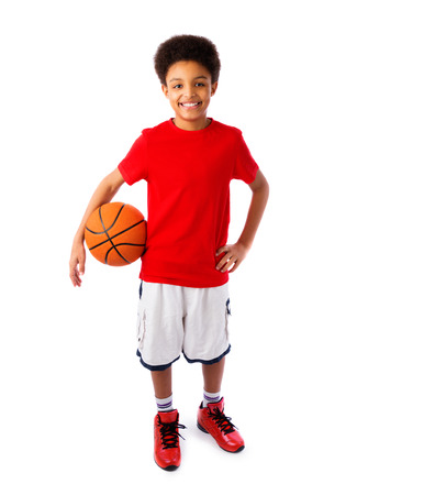 African American smiling teenager, basketball player posing with a ball in his hand isolated on white. Full body portrait.