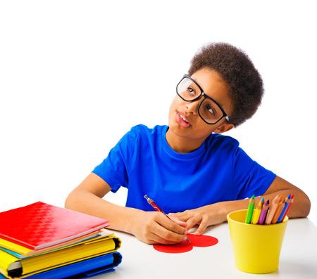 garcon africain: Handsome African American School Boy écrire un message à coeur de Valentines, Saint Valentin. Isolé, sur fond blanc, avec copie espace.