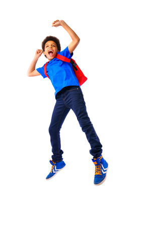 African American school boy, teenager smiling and jumping happy,education and school concept. Isolated, over white, with copy space. Full body portrait.