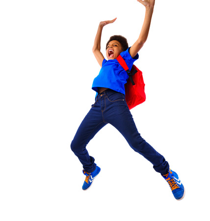 scholar: Excited African American school boy jumping happy, hands up, hanging on a board. Studio shot, isolated, over white, with copy space. Stock Photo