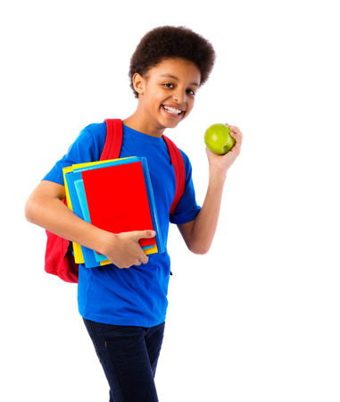 satchel: Happy African American school boy, teenager with colorful books, school bag and apple. Education and school concept. Stock Photo