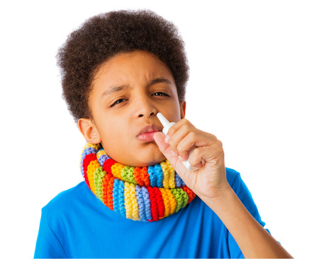 African American boy with nasal spray and colorful scarf, concept of allergy and flu. photo