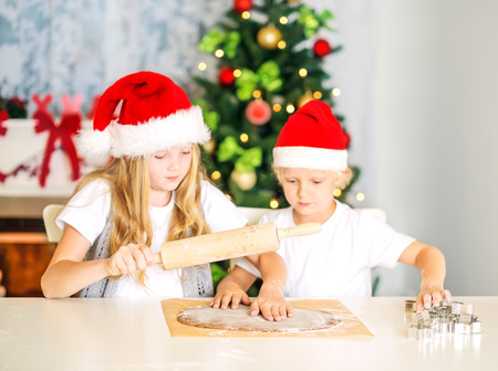 Children with Christmas Hats rolling dough, preparing cookies at home, with decorated Christmas Tree and Chimney at background. Selective focuse. photo
