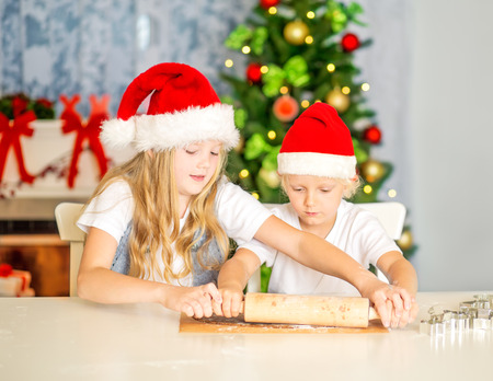 little dough: Children with Santa Hats rolling dough, preparing cookies at home, with decorated Christmas Tree and Chimney. Selective focuse.