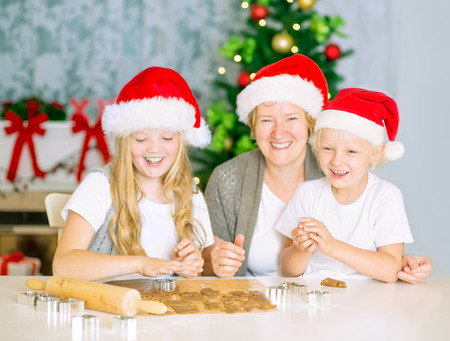 Mom with kids baking Christmas cookies, happy family of three with Santa Hats at home, having fun. photo