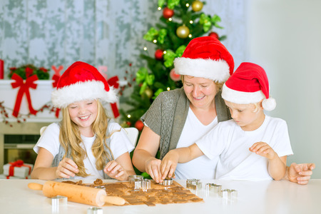 Happy mom with kids baking Christmas gingerbread cookies at home, with Santa Hats, chimney and decorated Christmas Tree. photo