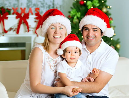 Portrait of Christmas happy family of three. Mother, father and son smiling, with Santa Hats, Christmas Tree and Chimney at background. photo