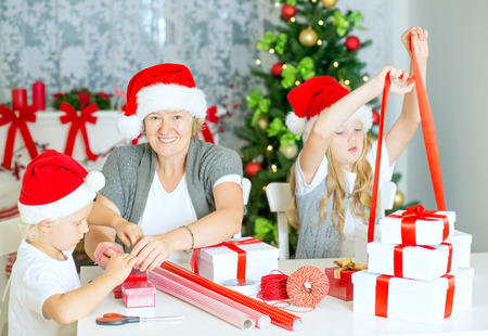 x mas: Happy Family of three, mom with children wrapping Christmas gifts at home, with Santa Hats and decorated Christmas Tree. Stock Photo