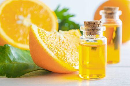 Natural orange essential oil in bottle and cut oranges fruit on white wooden table. Standard-Bild