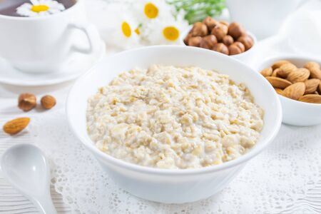 Oatmeal with nuts in bowl on white wooden table. Stock Photo