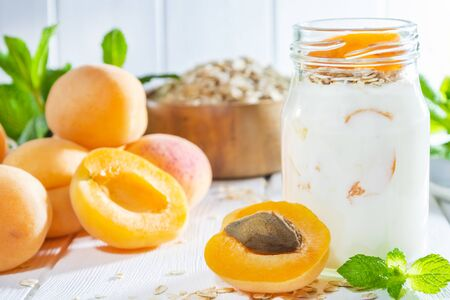 Oatmeal milkshake, smoothie or yogurt with fresh apricot on a white wooden background.