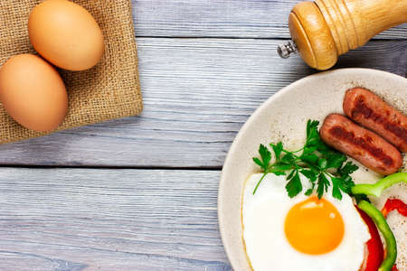 sunny side up. Fried eggs with sausages and vegetables on a light wooden table. High quality photo
