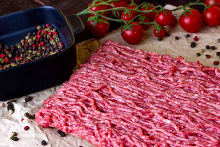 Minced meat on craft paper which lies on a wooden light table. Red hot chili peppers together with peppercorns