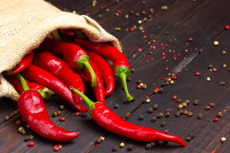 Red hot pepper in a bag on a dark wooden table. Chili. Standard-Bild