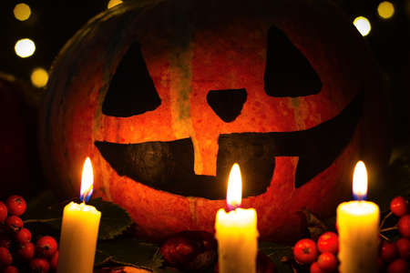Creepy smiling pumpkin in the candlelight for halloween.