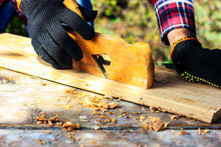 A man in the backyard is working the wooden planks with a plane. DIY Stok Fotoğraf