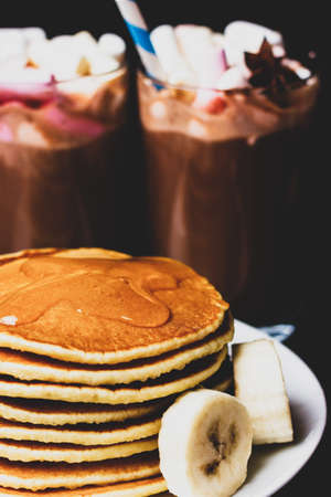 Pancakes with honey and banana slices on a background of sweet cocktails. Morning breakfast Banque d'images